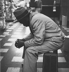 Black-man-on-suitcase-left-profile